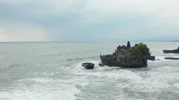 Aerial Dolly Shot Closing in on Tanah Lot Temple on a Dark Rocky Cliff in Rough Ocean with Large