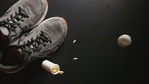DOPING: Behälter mit Pillen fällt in der Nähe von Turnschuhen