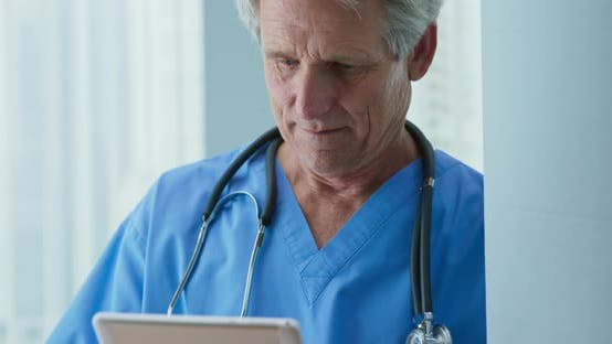 Thumbnail for Close up on doctor as he reads patient medical history on tablet computer