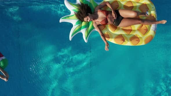 Top View of Joyful Girls Lying on Floaties in Pool