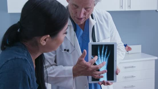 Doctor using tablet computer with x-ray of hand explaining arthritis to patient