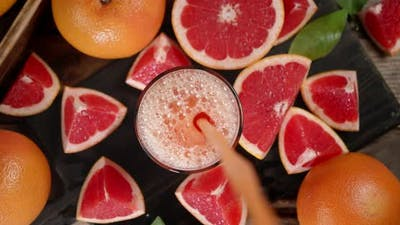Grapefruit Juice Poured Into a Glass with Slices of Fresh Grapefruit