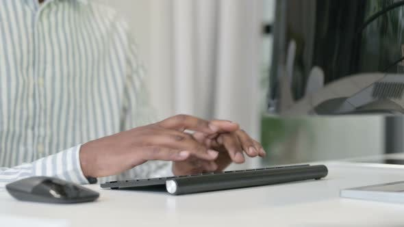 Close Up of African Man Using Mouse and Keyboard