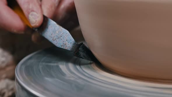 Thumbnail for Man Potter Working with a Pot Using a Putty Knife - Making a Sharp Border