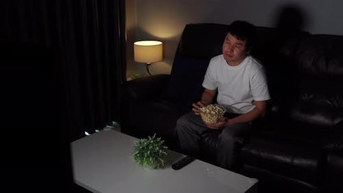 shocked young man watching TV movie on sofa at night