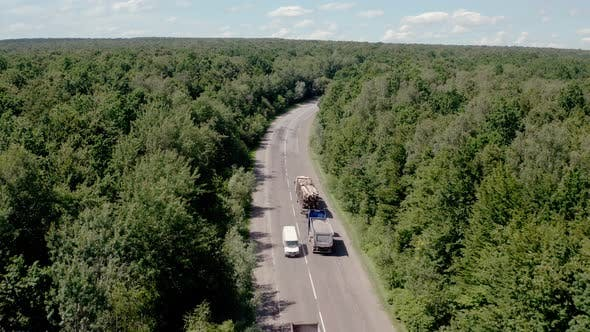 Thumbnail for Aerial View of White Truck with Cargo Semi Trailer and Several Cars Moving on Road in the Forest