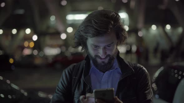 Thumbnail for Happy Caucasian Man Using Digital Device at Night in City