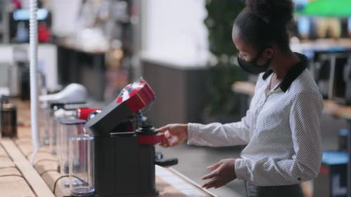 Female Shopper is Choosing Automatic Coffee Maker in Home Appliance Store Afroamerican Lady with