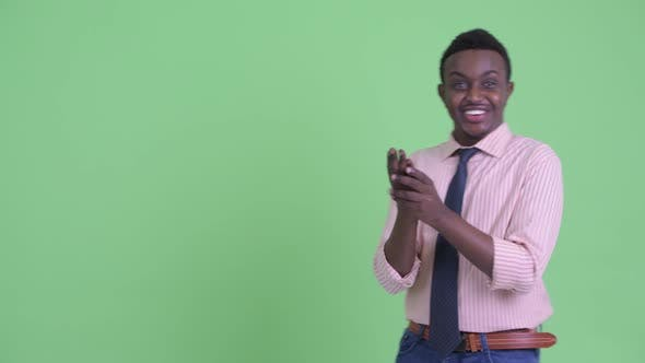 Happy Young African Businessman Snapping Fingers and Looking Surprised