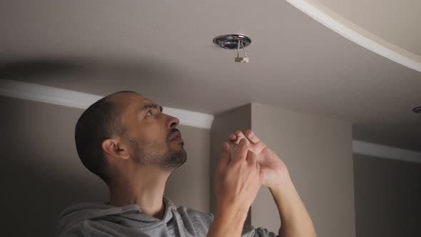 Young Man Repairing Cable Wiring and Installs or Replaces the Halogen Lamp on the Ceiling