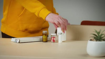 Young Woman Putting Medicine Into Box