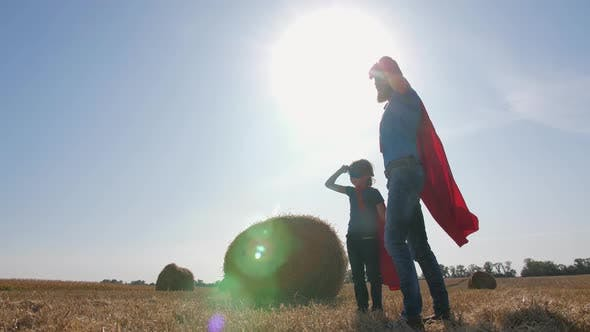 Father and Son in Superhero Costumes at Sunset