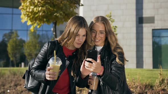 Thumbnail for Stylish Female Students Best Friends Drinking Fresh Juice Reading Something on the Smartphone