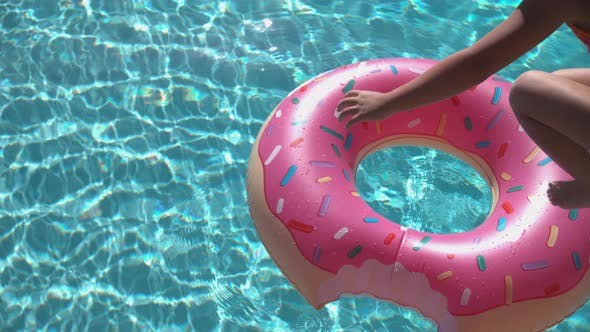Thumbnail for Girl jumping onto inflatable doughnut in super slow motion