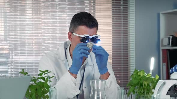 Smart Research Scientist in Magnifying Glasses Studying the Surface of the Stone in Modern Lab