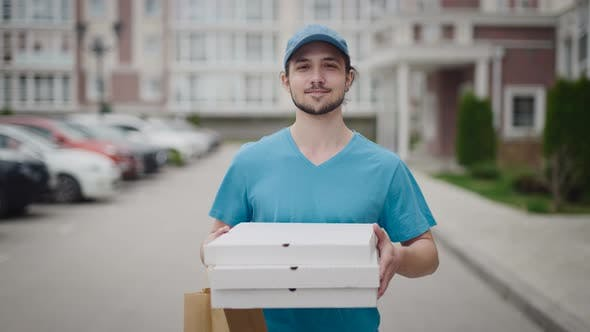 A Young and Energetic Delivery Man Carrying a Pizza and a Bag of Groceries