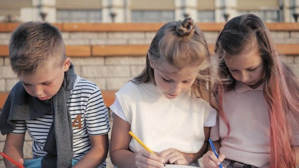 Cute kids doing artwork outdoors.