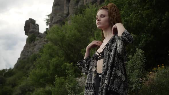 Thumbnail for Skinny Girl with Red Cornrows Against the Background of Greenery and Rocks