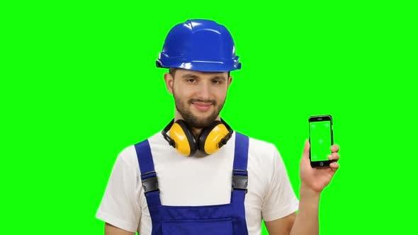 Thumbnail for Builder hält ein Telefon in seinen Händen und zeigt einen Daumen nach oben. Grüner Bildschirm. Mock Up
