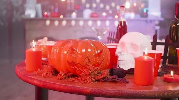 Totenkopf und Jack-O-Laterne auf einem Holztisch in einem Halloween dekoriert Pub