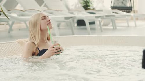 Charming Blonde Woman Resting in Jacuzzi with Soft Drink