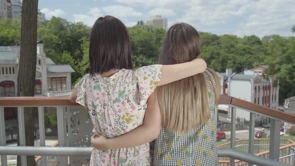Thumbnail for Two Attractive Girls Standing Outdoors Together Hugging and Talking, Admiring Beautiful Cityscape