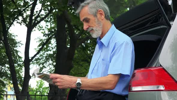 Thumbnail for Senior Man Sits in the Trunk and Reads a Newspaper - Trees in the Background