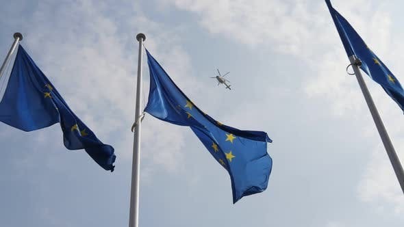Thumbnail for Three EU Standards Like Symbols with a Police Chopper on the Backdrop in Slo-mo