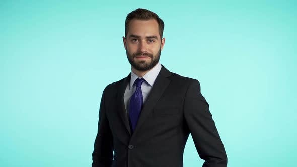 Cover Image for portrait of young successful confident businessman with beard isolated on blue studio