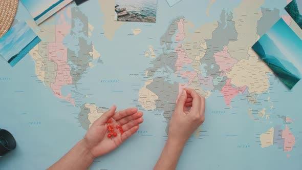 Woman Pushing Pins on World Map