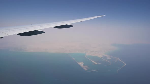 the Plane Flies at High Altitude. View From the Window on the Wing. Turquoise Water Under the Wing