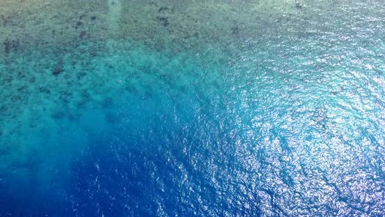 Tropical birds eye copy space shot of a white sand paradise beach and blue sea background in 4K