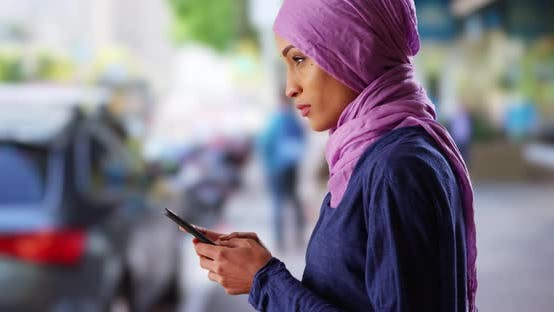 Thumbnail for Black female in her 20s wearing hijab, texting on cellphone on urban street