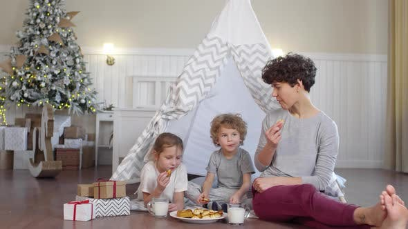Cover Image for Happy Mother and Kids Eating Cookies in Room with Teepee and Christmas Tree
