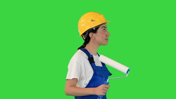 Female House Painter with Paint Brush Walking Looking What to Paint on a Green Screen Chroma Key
