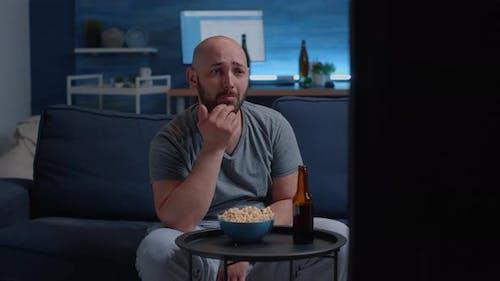 Sad Guy Watching Drama Movie on TV Crying