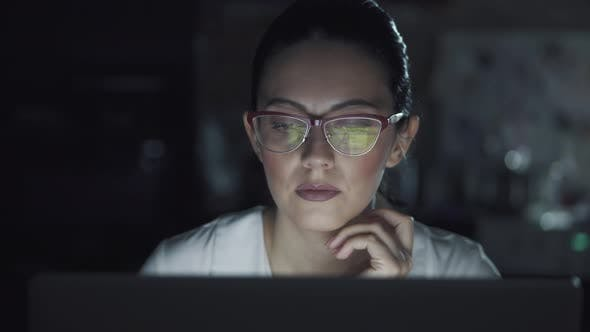 Cover Image for Woman in Glasses Works on a Laptop in the Dark. Portrait of a Girl Spending Time at the Computer