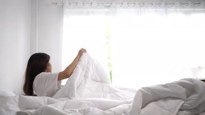 Young woman wake up in morning and stretches on bed