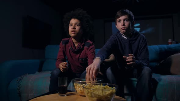 Scared Teens Eating Popcorn During Horror Movie