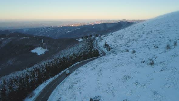 White Semitrailer Truck Fast Driving Toward on Slippery Winter Asphalt Mountain Highway