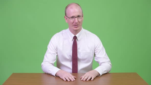 Thumbnail for Happy Mature Bald Businessman Talking Against Wooden Table