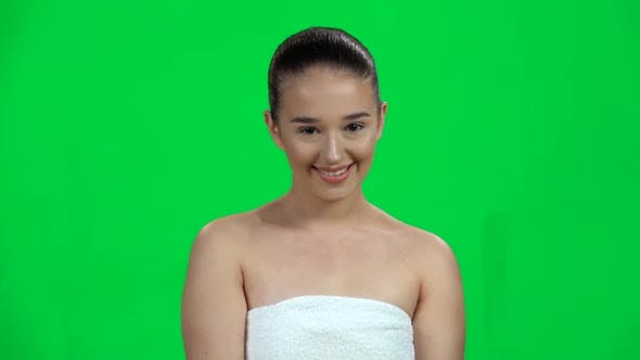Thumbnail for Attractive Woman in White Towel Smiles Coquettishly Looking at the Camera, Green Screen. Slow Motion