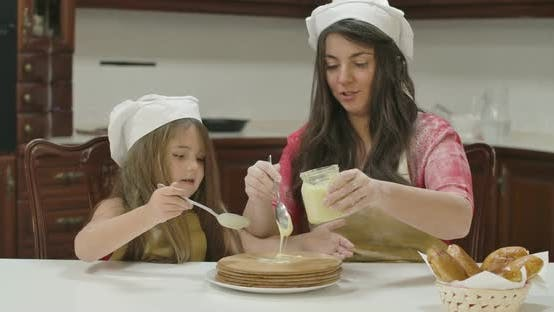 Cover Image for Caucasian Mother and Daughter Applying Condensed Milk on Baked Cake