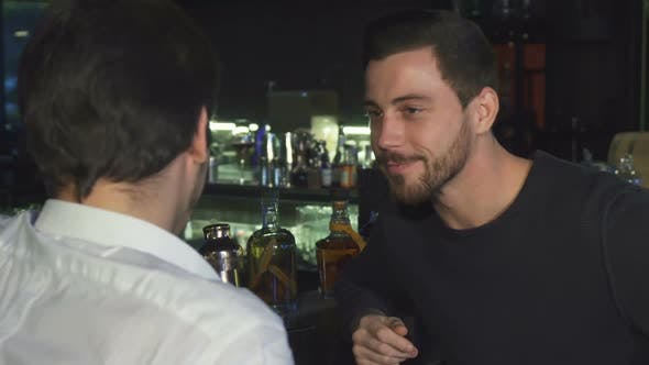 Thumbnail for Young Male Friends Talking While Having Drinks Together at the Bar