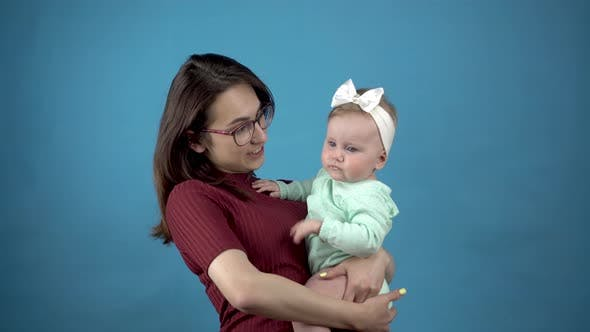 A Young Mother Holds a Baby in Her Arms. Woman with a Daughter on a Blue Background.