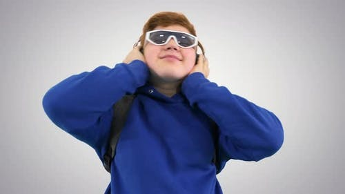 Boy in Stylish Sunglasses Listening To Music with Headphones on Gradient Background.