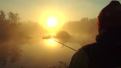 Unrecognizable Man Fishing in Lake at Dawn