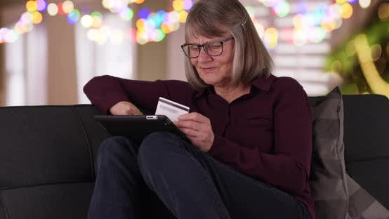 Thumbnail for Happy mature lady on couch holiday shopping online with portable tablet device
