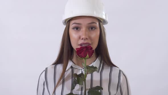 Thumbnail for Young Beautiful Woman in Construction Hat Holding a Red Rose in Her Hands and Happy