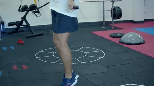 Legs of Male Boxer with Skipping Rope. Fighter Doing Jump Rope Exercises in Dark Gym. Warming Up and